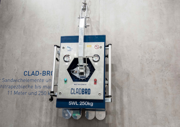 Compact panel lifter for construction site CLAD-BRO in front view in front of gray concrete wall