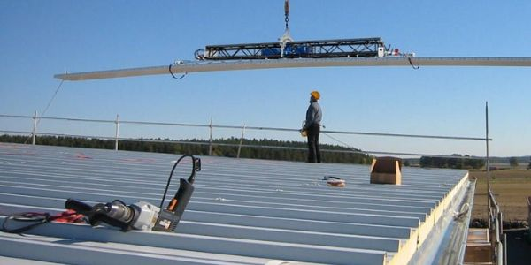 Man operates CLAD-BOY 2.0 vacuum lifter on construction site for panels on roof and wall